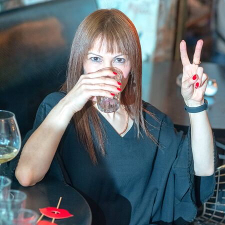 Closeup shot of mature happy beautiful woman showing peace gesture and drinking a glass of water in restaurant. 写真素材