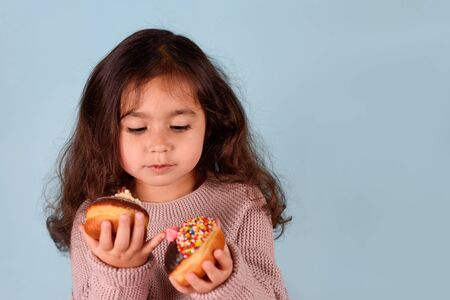 Little happy cute girl eating donuts on blue background. Child having fun with donut. Stock Photo