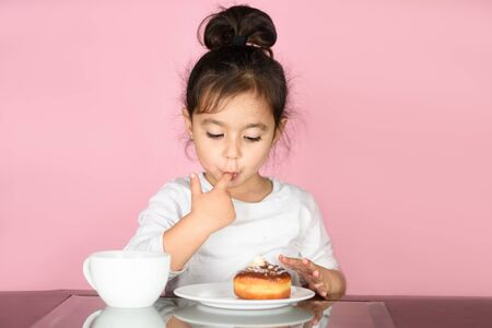 Little happy cute girl eating donut, drinking tea, licks her fingers, on which sweet cream is stuck. Selective focus on child.