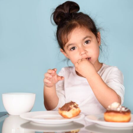 Little happy cute child eating donut with chocolate glaze and drinking tea on blue background. Selective focus on toddler girl licks her fingers.