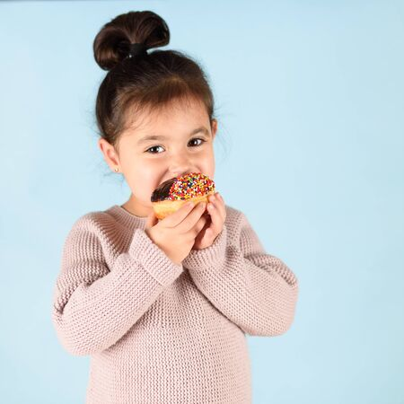 Happy little cute child holding donut and eating.