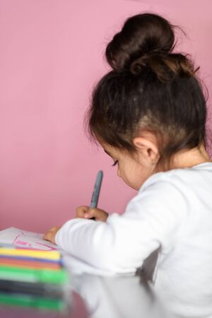 Little girl drawing, cozy moment of life. Selective focus.