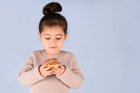 Happy little cute child holding donut and eating on blue background.