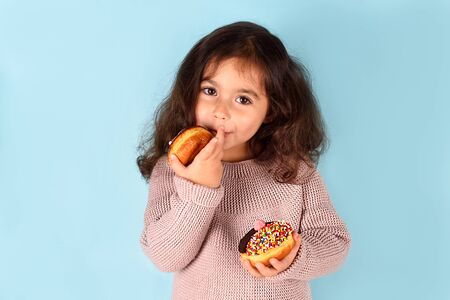 Little happy cute girl with curly hair eating donut licks her fingers, on which sugar is stuck. 写真素材