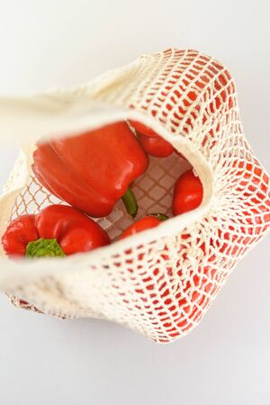 Natural reusable cotton mesh eco grocery bag with fresh sweet red peppers. Top view. 写真素材