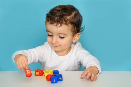 Jewish boy playing with colorful wood dreidel. Kid celebrating Hanukkah Israel holiday.