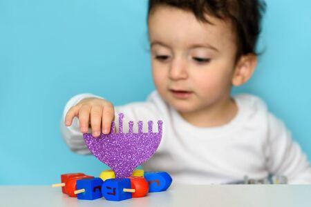 Jewish Boy Play With Festive Hanukkah Blue Purple Menorah And Colorful Wood Dreidels. Selective Focus.