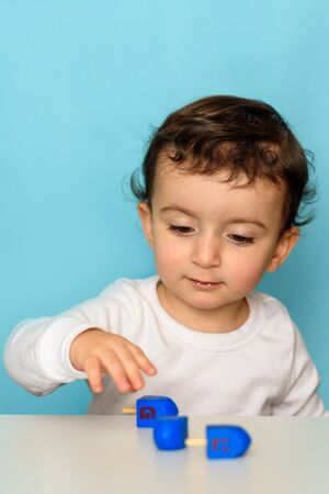 Jewish curly haie sweet little boy playing with blue color dreidel at home. 写真素材