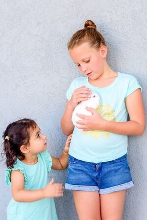 Teenager child holding a cute little white rabbit. Two happy young girls playing with bunny. 写真素材