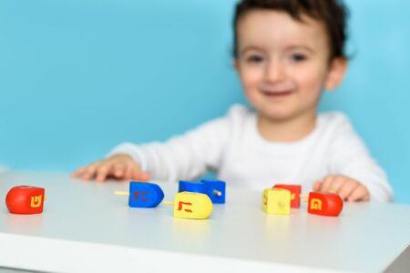 Little jewish boy playing with colorful wood dreidel. Selective focus on dreidel. 写真素材