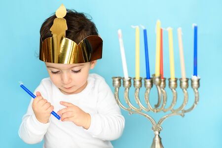Kid celebrating Hanukkah Israel holiday. Little jewish boy puts candles on traditional menorah. 写真素材