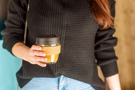Close-up of businesswoman holding reusable takeaway glass coffee cup. Zero waste concept. Eco cup .