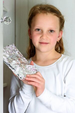 Girl with Afikoman is a half-piece of matzah which is broken of the Passover Seder. In many families the father takes the afikoman and hides it. The child that finds the afikoman receives gift. 写真素材