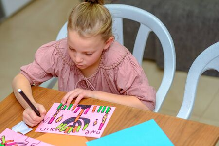 Needlework, crafts children.Little girl create a greeting card image of the Jewish holiday of Hanukkah. Kid pastes stickers, glue candles and drawing menorah, dreidel, oil jar on paper on wooden table