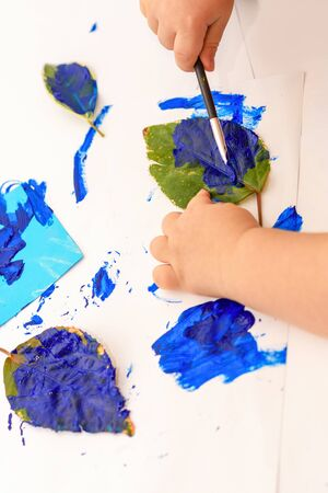 Little child painting leaves blue, arts and crafts. Classic Leaf painting art.