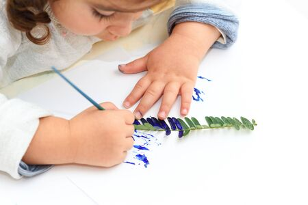 Little girl painting leaves blue color, crafts and art therapy. Classic Leaf painting art. Child of stock contributor painting green leaves trendy blue color 2020.