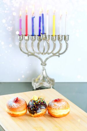 Hanukkah celebration concept. Close up view of tasty donuts with jam and chocolate on background menorah traditional candelabra with lighting candles. 写真素材