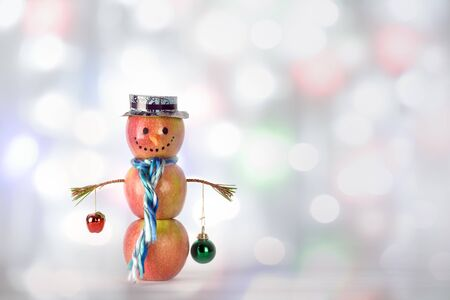 Concept of Sustainable, Zero waste, Vegan Christmas. Happy Creative snowman from apples in a hat and a scarf with balls in hands standing on bokeh colored light background. 写真素材