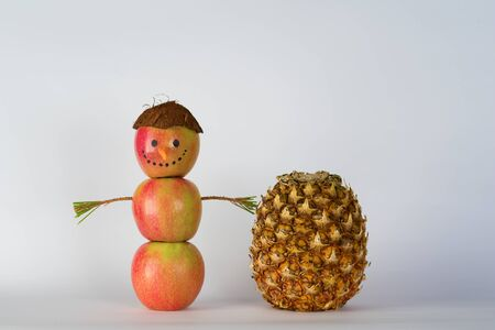 Concept of Sustainable, Zero waste, Summer Vegan Christmas. Creative snowman from apples, apple man in a hat from coconut and a pineapple standing on white background.