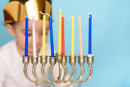 Kid celebrating Hanukkah Israel holiday. Little Jewish boy puts candles on traditional menorah. Selective focus on menorah with eight candles. 写真素材