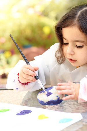 Portrait of little child painting on stone with blue color. Kid drawing on a stone, summer outdoor.
