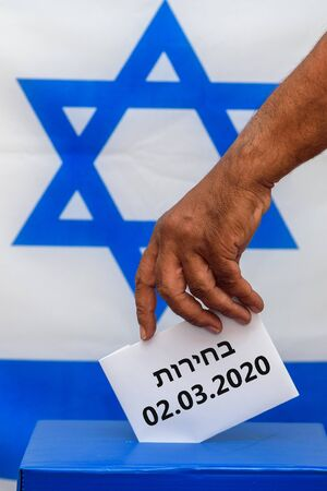 Israeli man putting a ballot in a ballot box on election day. Close up of hand with white votes paper on Israel flag background. Hebrew text Election 02.03.2020 写真素材
