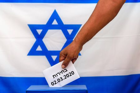 Israeli man putting a ballot paper in a ballot box on election day, third 2020 Israeli vote. Close up of hand with white votes paper on Israel flag background. Hebrew text Election 02.03.2020