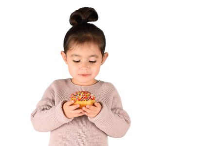 Happy little cute child eating donut with bright candies on isolated white background. Banco de Imagens