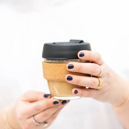 Woman hands hold reusable glass coffee cup. Sustainable living. Eco friendly, zero waste concept. 写真素材