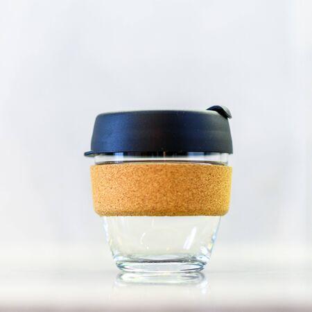 白い背景にプラスチック製の蓋が付いた再利用可能なガラステイクアウトコーヒーカップ。