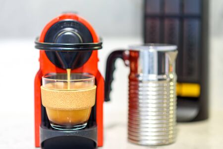 Coffee machine preparing fresh coffee and pouring into reusable glass coffee cup at restaurant, bar, pub or kitchen. Zero waste concept.