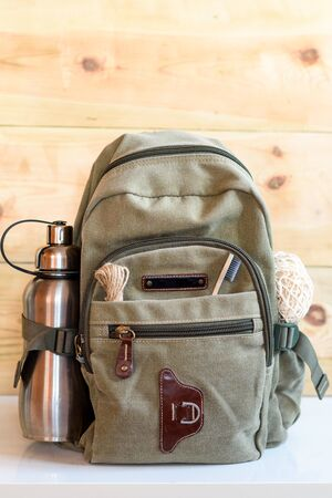 Zero waste travel. Backpack with stainless steel plastic free reusable water bottle, natural reusable cotton mesh grocery bag, eco-friendly bamboo toothbrush, rope jute string twine hemp linen cord.