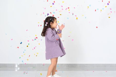 Portrait of a cheerful beautiful little girl wearing party dress standing under confetti rain and celebrating over white background.