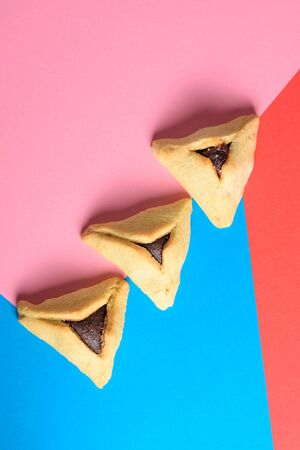 Purim holiday concept. Creative arrangement of Hamantash on red,pink and blue paper background. Hamantaschen triangular pastries also called Hamans pockets or Oznei Haman-Hamans ears.