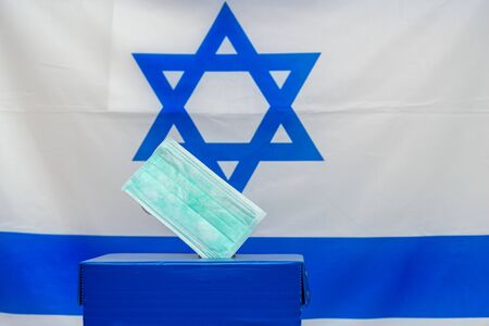 Elections Israel. Disposable face mask in a box for ballot in election on Israel flag background. Israelis quarantined for coronavirus will get voting booths for March election. Banque d'images