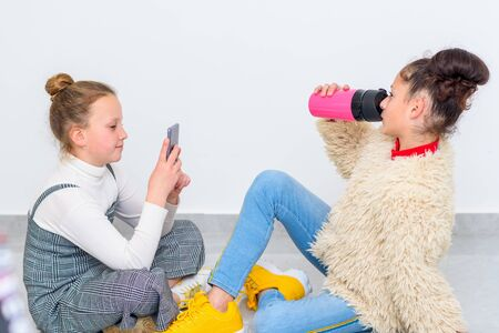 Close up portrait of two diverse teen girls. Young kid uses smart phone to take portrait of black hair teenage drinking hot coffee from reusable pink cup. Stock Photo
