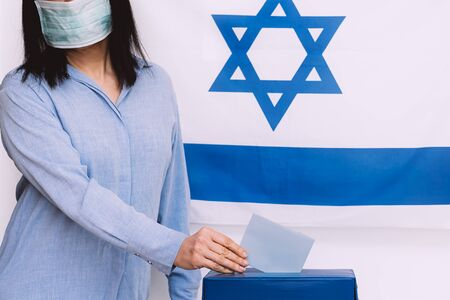 Israeli woman with face medical protected mask putting ballot in a ballot box on election day on Israel flag background.Israelis quarantined for coronavirus will get voting booths for March election.