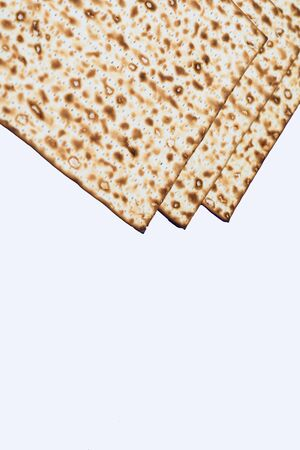 Passover matzo, matzah, or matza unleavened flatbread isolated on white background. Matzah is part of Jewish cuisine and forms an integral element of the Passover festival.