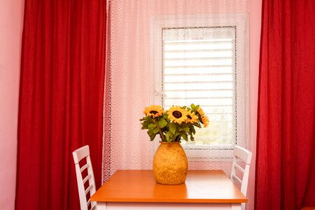 Flowers In Vase On Table At Home. Sunlowers On Table In Bright Cozy Red Pink Color Room. Imagens