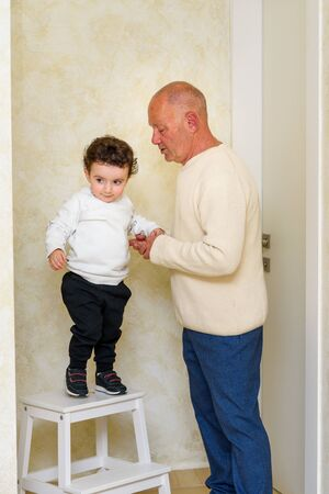 Funny little boy jumps off stepladder, holding hands with grandfather. Happy family at home enjoying simple moments. 版權商用圖片