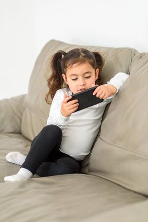 Beautiful Small Girl Attending To Online Class From Home. Little Child With Cell Phone On Couch.