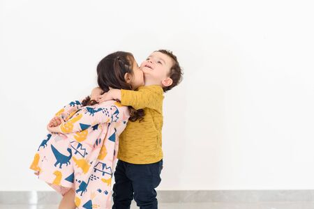 Portrait happy brother and sister huging. Kissing little boy and girl. Siblings day.