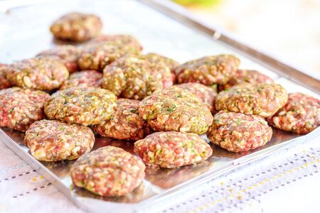 Raw homemade kebab or meatball with green parsley, garlic, spiced and sliced onion in tray on table. It is a very popular in Middle East. BBQ outdoor party.