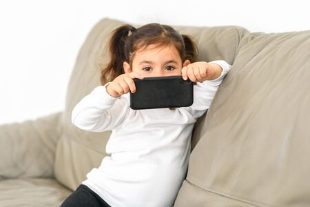 Little girl taking photos on a cell phone in the home.