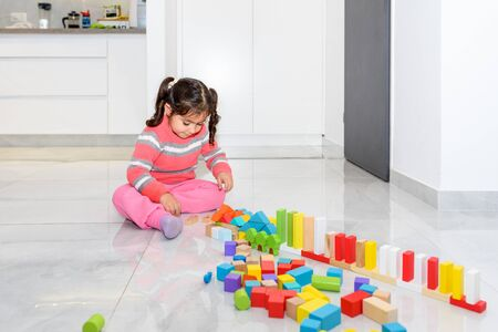 Home games for kids. Creative child play with wooden toy building blocks in home during corona virus. Foto de archivo