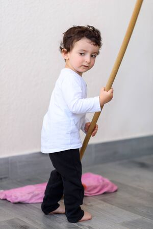Portrait of little funny boy cleaning tile floor with mop and rag. Reklamní fotografie