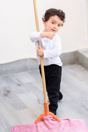 Portrait of little smiling boy cleaning tile floor with mop and rag.