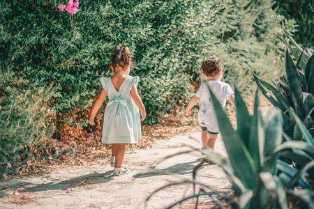 Back to preschool. Back view cute little children going to school with fun. Reklamní fotografie