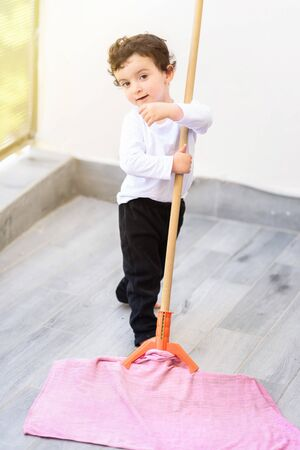 Portrait of little smiling boy cleaning floor at home.