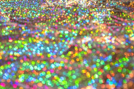 Abstract blurred of silver glittering shine bulbs lights background. Sparkle silver colorful glittering background. Real defocused lights.